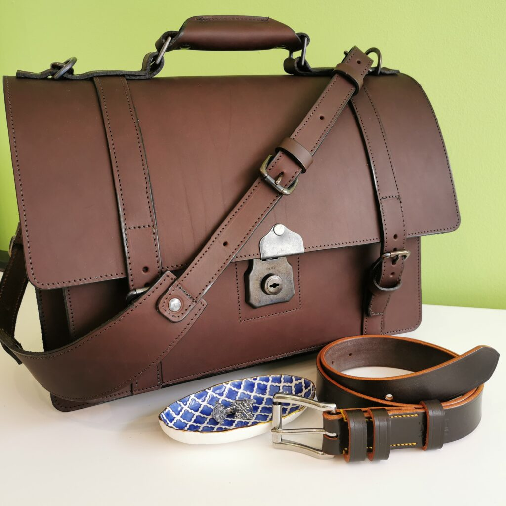 Brown and silver group picture of: The Full Monty briefcase, Dark Havana leather belt, Blue Alhambra porcelain trinket tray and Celtic Knot cufflinks
