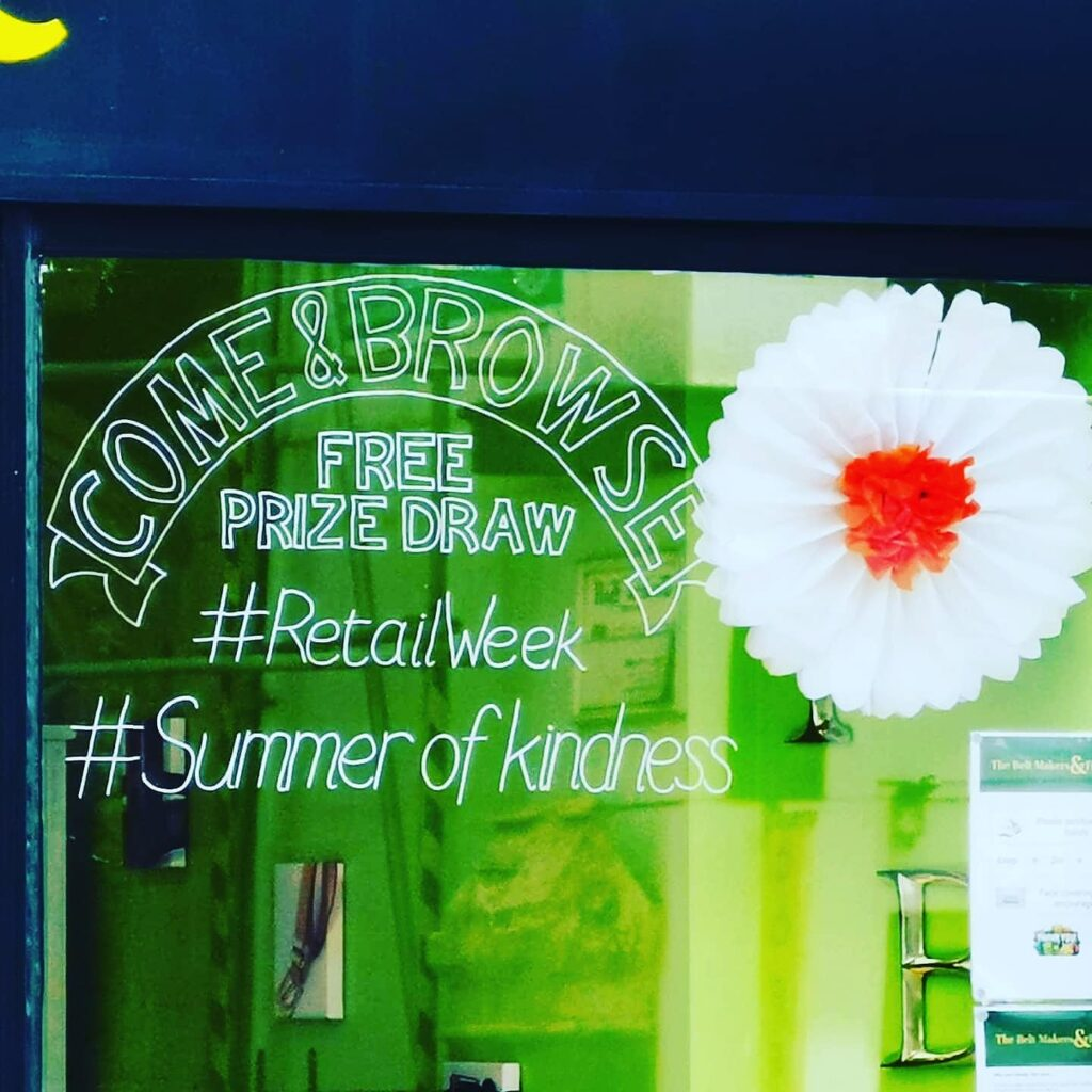 Close up of our shop window with handwritten chalk pen banner stating Come & Browse, Free Prize Draw, #RetailWeek, #SummerofKindness
